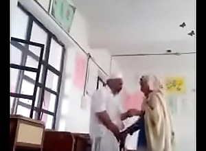 A 70 yrs old man sex roughly 30 yrs bold lady in classroom.